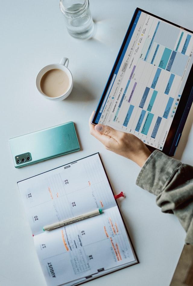 man sieht ein Kalenderbuch und ein Kalenderscreen auf einem Tablet, sowie ein Handy, eine Tasse Kaffee und ein Glas Wasser. Das Tablet wird von einer Hand gehalten.
