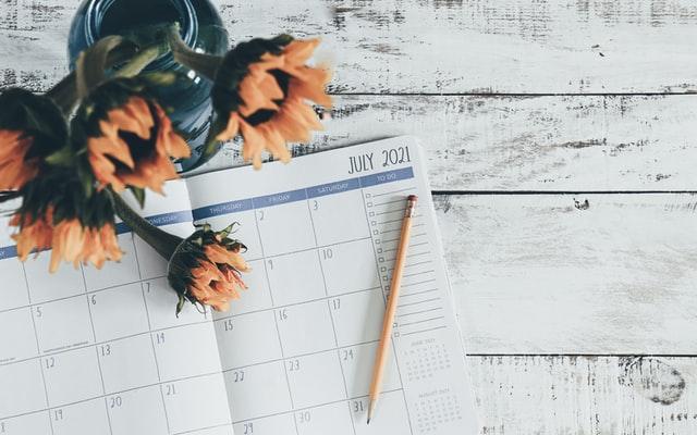 Sonnenblumen in einer Vase und ein Kalenderheft mit Bleistift auf einem weißgestrichenen Holztisch